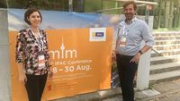 "Von links: Dr. Eva Klenk von SALT Solutions AG und Prof. Stefan Galka von der OTH Regensburg auf der ""9. IFAC Conference on Manufacturing Modelling, Management and Control"" (MIM) in Berlin."